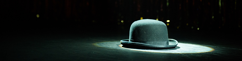 black bowler hat in spotlight on stage