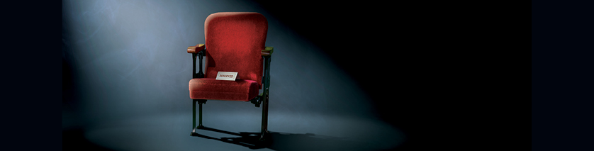 red reserved theatre seat on stage in white light